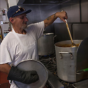 Homeless Soap Kitchen in Atlantic City. Volunteer Cook preparing food in advance. <br /> <br /> The Kitchen was founded by a former casino chef, Jean Webster, 74, found her calling when she saw a man rummaging through a garbage can in search of food.