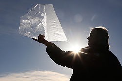 © Licensed to London News Pictures. 28/12/2017. Shepton Mallet, UK. Helen Trott holds ice formed in a frozen flooded field while out walking near Shepton Mallet. Photo credit: Jason Bryant/LNP