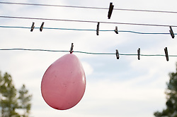 Pink balloon hanging on a clothesline