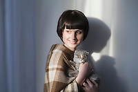 Woman in blanket stands holding kitten