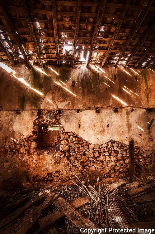Beams of sun light passing through a rotten roof of a haystack.