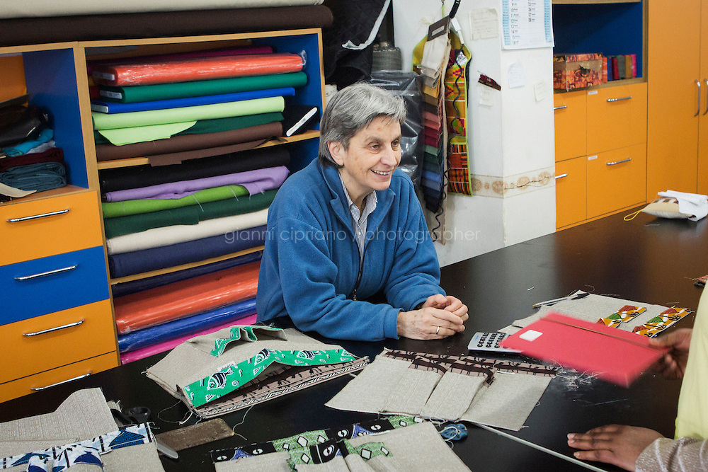 CASERTA, ITALY - 25 FEBRUARY 2015: Sister Rita Giaretta, founder of Casa Rut and of the New Hope tailor's shop, listens to a young immigrant woman at the tailoring studio in Caserta, Italy, on February 25th 2015.<br /> <br /> New Hope is an ethnic tailor's shop that makes a variety of colourful products working mainly african fabrics. The New Hope social cooperative, founded in 2014, promotes a training workshop for your immigrant women, many of which have children, that want to integrate in Italian society.