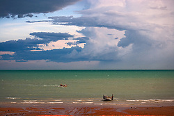 Storms build at Town Beach, in Broome, Western Australia, as boaters return to shore.  The town is lacking a marina.