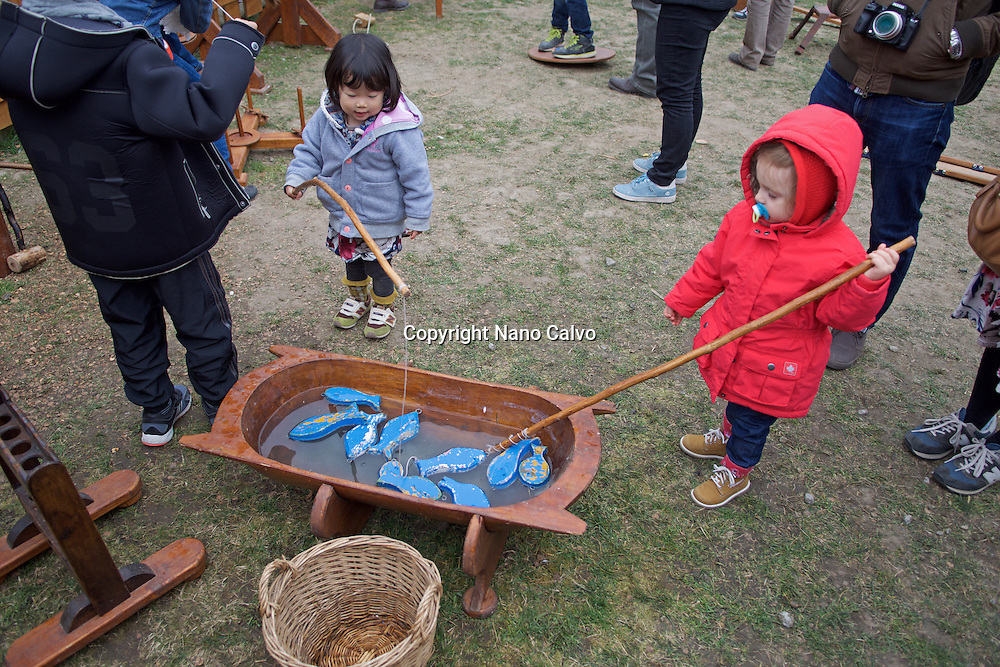 Wood fishing game for kids. <br /> <br /> Traditional costumes and folk traditions at Easter Festival in Holl&oacute;kő, UNESCO World Heritage-listed village in the Cserh&aacute;t Hills of the Northern Uplands, Hungary.
