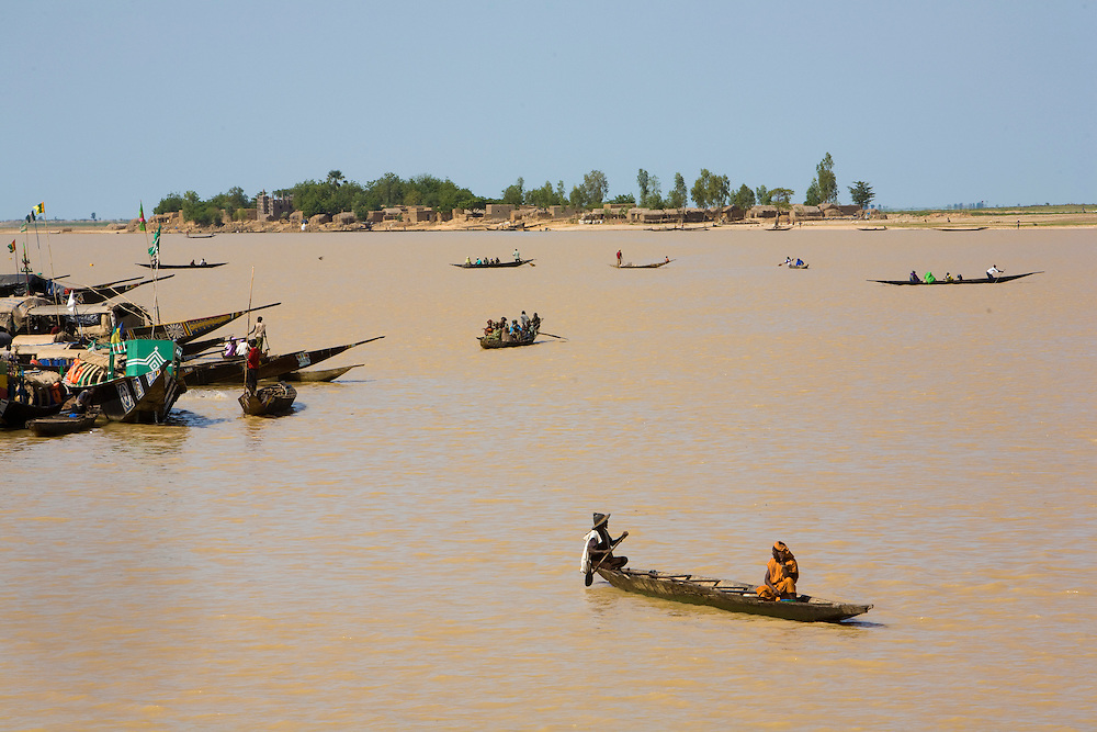 "Tipical ""pinasses"" canoes navigate in  Mopti's harbor. At the confluence of the Niger and the Bani rivers, between Timbuktu and S?gou, Mopti is the second largest city in Mali, and the hub for commerce and tourism in this west-african landlocked country."