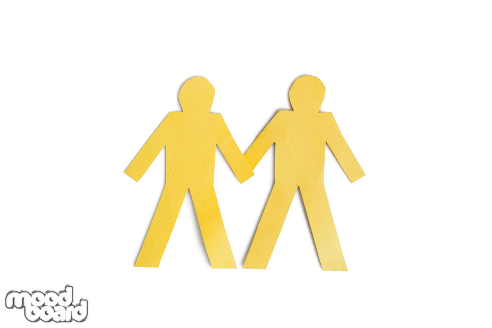 Two yellow paper cut out figures holding hands over white background