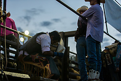 A cowboy takes a moment to pray prior to competition.