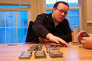 Matthew Becker makes his play during a game of Dominion.  Becker, 29, prefers strategy games like Dominion, Risk and Axis and Allies.  He has a tendency to play defensively and switch alliances, earning him the title 'Becker-the-betrayer.'  December 7, 2013.  Photo by Andrew Welsch/NYCity Photo Wire
