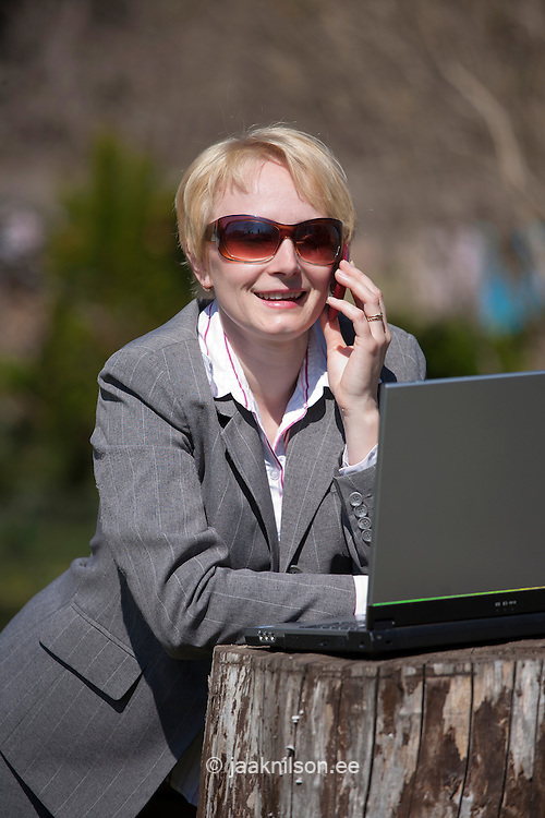 Happy Smiling Businesswoman Talking Mobile Phone by Laptop Computer