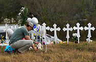 Kyle Dahlberg adjusts a Teddy bear placed at a row of memorial crosses near the site of the shooting at the First Baptist Church of Sutherland Springs, Texas, U.S., November 7, 2017.  REUTERS/Rick Wilking