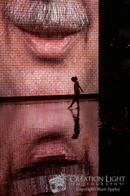Crown Fountain was designed by Spanish, Catalan artist Jaume Plensa and opened in July 2004. The fountain consists of two 50-foot glass block towers at each end of a black granite shallow reflecting pool. The towers project video images from a broad social spectrum of Chicago citizens having water periodically flow through a water outlet in the screen to give the illusion of water spouting from their mouths. This is a reference to the traditional use of gargoyles in fountains, where faces of mythological beings were sculpted with open mouths to allow water, a symbol of life, to flow out. The collection of faces, Plensa's tribute to Chicagoans, was taken from a cross-section of 1,000 residents...The fountain, which is at the southwest corner of Millennium Park at Michigan Avenue and Monroe Streets, is a favorite of both children and families. Its use of water is unique among Chicago's many fountains, in that it promotes physical interaction between the public and the water. Both the fountain and Millennium Park are highly accessible because of their universal design. The fountain is a public play area and offers people an escape from summer heat and allows children to frolic in the fountain's water.