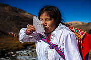 A woman drinks water from a piece of ice of thawing of the mountain glacier Sinaqara during the celebration that worships the Lord of Qoyllur Rit'i, in Cusco, Peru.