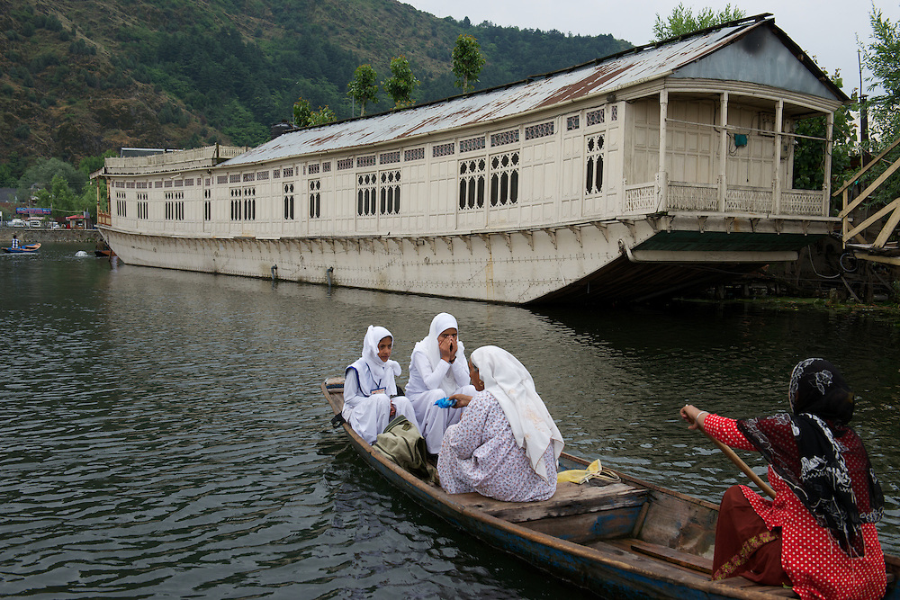 A mother paddles her children to school past the wooden houseboats moored around Dal Lake.