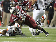 ATLANTA - DECEMBER 4:  Running back Marcus Lattimore #21 of the South Carolina Gamecocks is tackled by Daren Bates #25 of the Auburn Tigers during the 2010 SEC Championship at Georgia Dome on December 4, 2010 in Atlanta, Georgia. (Photo by Mike Zarrilli/Getty Images)