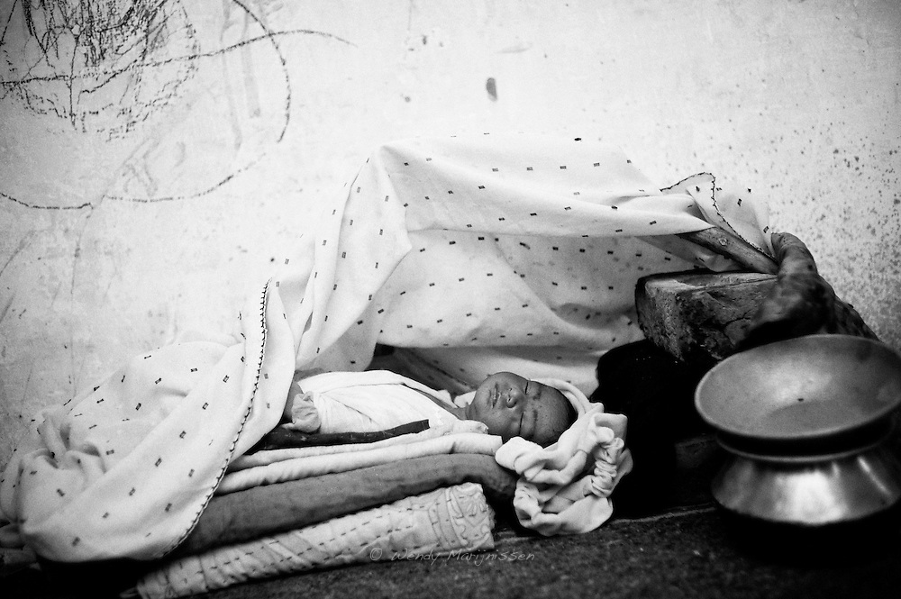A newborn baby sleeps in the Technical College used as temporary shelter for flood-affected families. <br /> Many rural families in the camps position their babies in this traditional way, lowering the head, believing it elongates the neck. They continue this practice despite being warned by doctors for the obvious health concerns for the baby. Karachi, Pakistan, 2010
