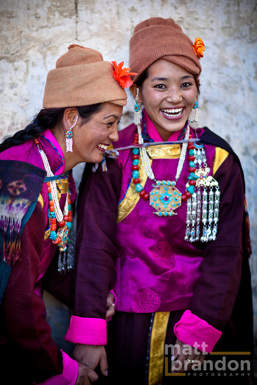 Two attractive Ladakhi women laugh and giggle in traditional costume.