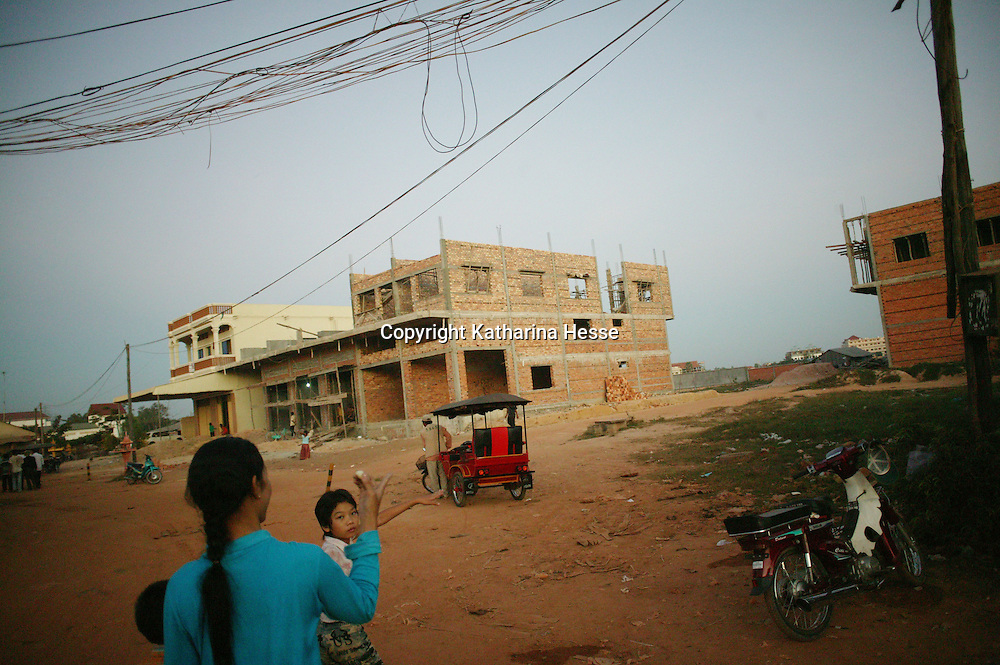 SIEM REAP, NOVEMBER-27: a woman leads her daughter to a building under construction in Siem Reap, November,27, 2006, Cambodia...