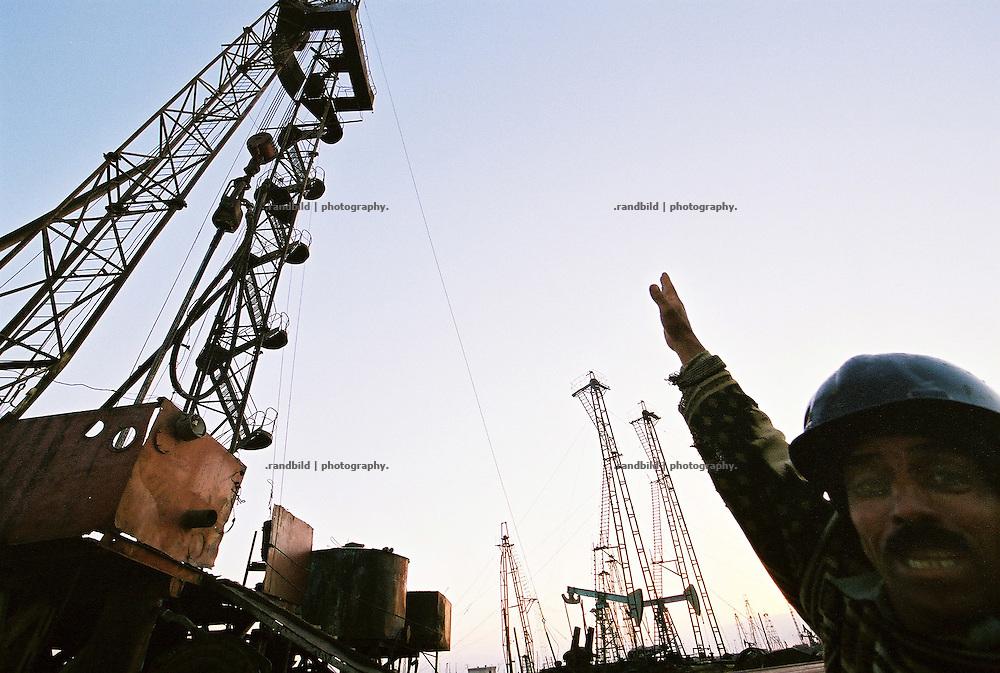 Das Selimkhanow-Ölfeld im Licht der aufegehnden Sonne. Vor über 100 Jahren begann hier im Süden der aserbaidschanischen Hauptstadt Baku der erste Ölboom. Noch immer fördern hier Arbeiter Erdöl mit abenteuerlich alter Technik das schwarze Gold aus dem Untergrund. Überall rosten alte Bohrtürme vor sich hin, schwarze Seen aus Öl verseuchen die Landschaft. Abwässer werden in das nahe gelegegen Kaspische Meer geleitet. Eine apokalyptische Landschaft. The old Selimkhanov oilfield near Baku, Aserbaijan.