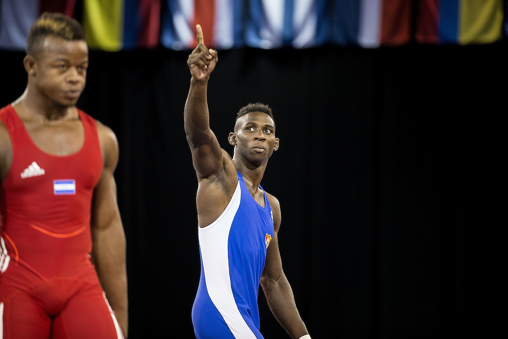 Alan Vera (R) of Cuba celebrates his bronze medal win over Oscar Martinez of Honduras in the 85kg class of the men's greco-roman wrestling at the 2015 Pan American Games in Toronto, Canada, July 15,  2015.  AFP PHOTO/GEOFF ROBINS