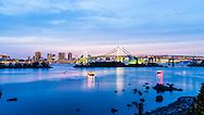 Tokyo Rainbow Bridge illuminated at twilight sunset with boats floating on Tokyo Bay