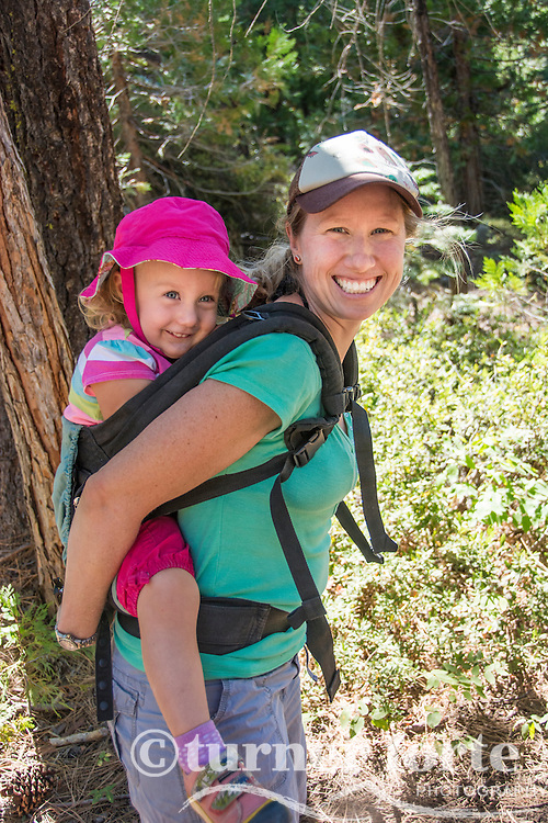 Portrait of mother carrying toddler daughter on back in pack on hike to Horsetail Falls, Strawberry, California.
