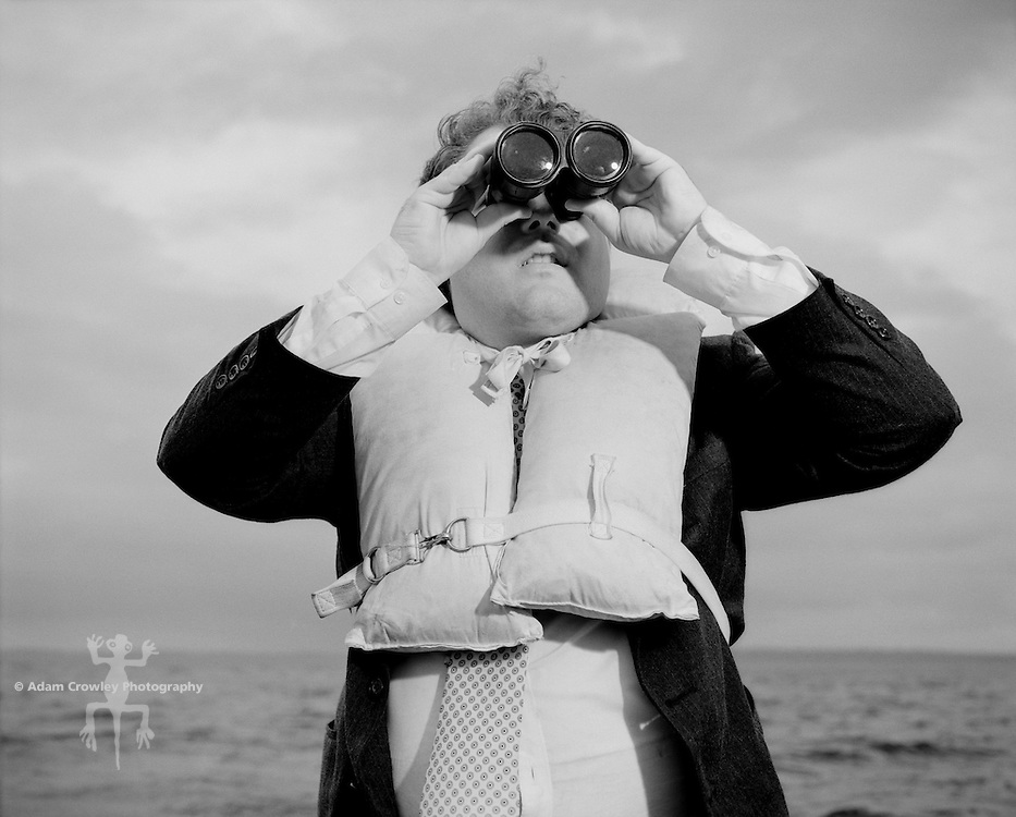 Businessman in life jacket, looking through binoculars (B&W)