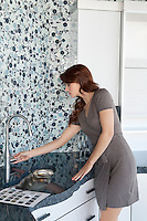 Young woman looking at faucet in model home kitchen