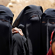 Yemeni women traditionally covered, except for younger girls, outside of a wedding in Wadi Hadramaut.