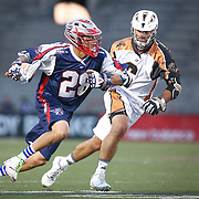 Brent Adams #28 of the Boston Cannons keeps the ball away from Stephen Ianzito #6 of the Rochester Rattlers during the game at Harvard Stadium on August 9, 2014 in Boston, Massachusetts. (Photo by Elan Kawesch)