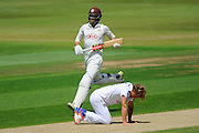 Surrey's Ben Foakes runs past Hampshire bowler Gareth Berg who is on his hands and knees, on reaching his 50 during the Specsavers County Champ Div 1 match between Hampshire County Cricket Club and Surrey County Cricket Club at the Ageas Bowl, Southampton, United Kingdom on 18 July 2016. Photo by Graham Hunt.