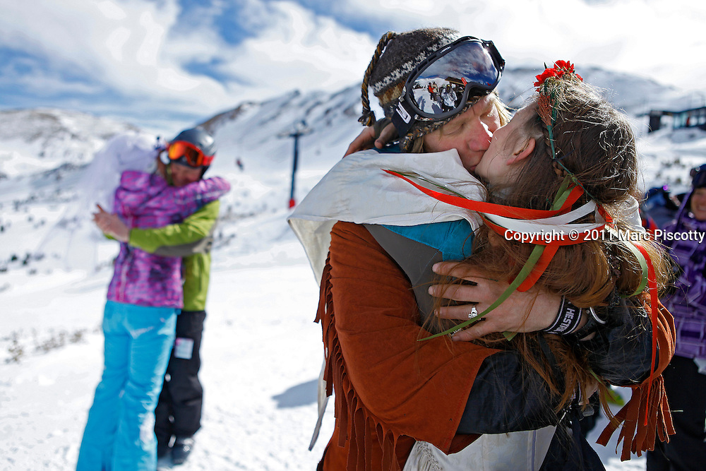 LOVELAND SKI AREA, CO - FEBRUARY 14: Elaine Vardamis of Nederland, Co. is kissed by her husband Dan Vardamis as the couple renews their vows with other couples atop Loveland Ski Area in Colorado at the 20th Annual Marry Me & Ski Free Mountaintop Matrimony on Valentine's Day Monday, February 14th. The mass wedding ceremony was held at noon at 12,050 feet outside of the Ptarmigan Roost Cabin at Loveland. More than 75 couples were pre-registered to get married or renew their vows high on The Continental Divide in this yearly Loveland tradition.  Following the ceremony couples were invited to a casual reception complete with a champagne toast, wedding cake and music. The couple was married about eight months ago at the County Clerks office in Boulder, Co. and this was their first official ceremony. (Photo by Marc Piscotty © 2011)