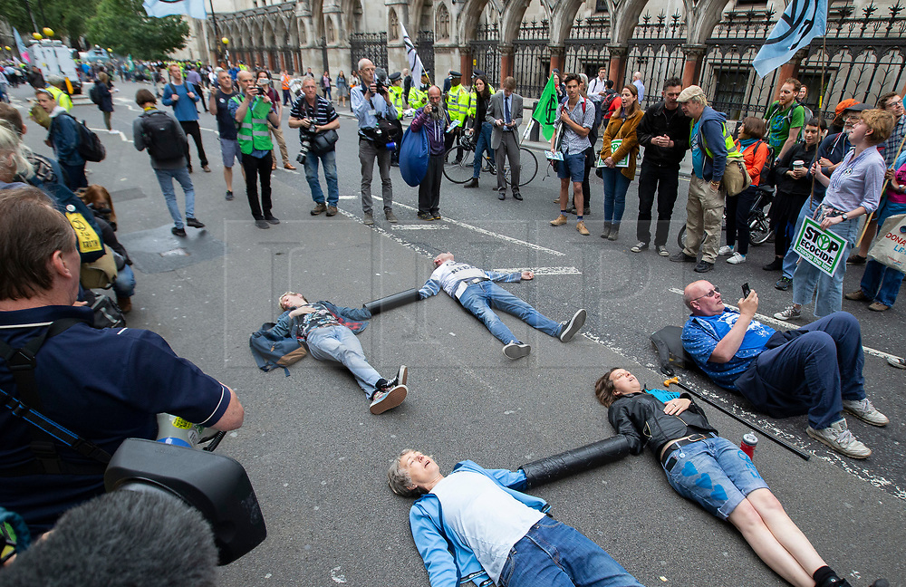 © Licensed to London News Pictures. 15/07/2019. London, UK. Extinction Rebellion protesters lock on outside The Royal Courts of Justice. They are campaigning against climate change.  Photo credit: George Cracknell Wright/LNP