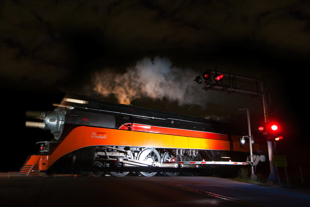"The famous SP 4449 4-8-4 ""Daylight"" steam locomotive billows smoke into the night sky as it speeds through Berwyn, IL on a late summer evening."