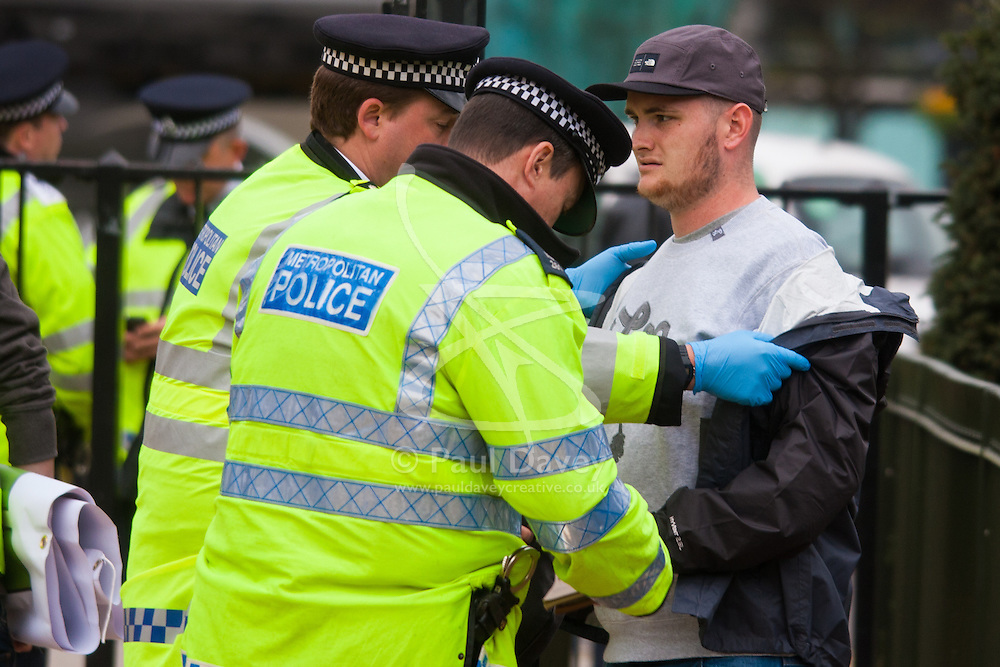 Hyde Park, London, April 19th 2015. Hundreds of cannabis users and their supporters gather at Speaker's Corner in Hyde Park for the annual London 420 pro-cannabis rally, under the watcful eye of Metropolitan Police officers, who kept a reasonably low profile, allowing the rally to continue without any serious incidents. PICTURED: Police search a man as he enters Hyde Park after a drugs dog had indicated he was possibly carrying illegal substances.