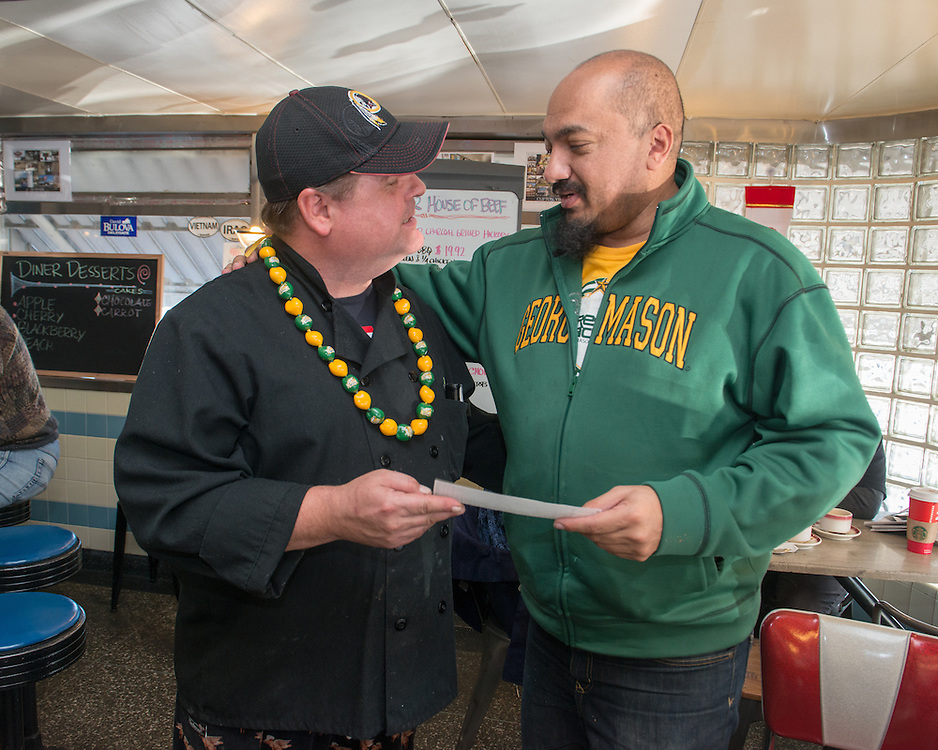 December 5, 2015 - Fairfax, VA - A day in the life of &quot;Doc Nix,&quot; aka Dr. Michael Nickens, the Director of the Athletic Bands for George Mason University.  John Wood presents a check in support of George Mason athletic bands to Doc Nix.<br /> <br /> Photo by Susana Raab