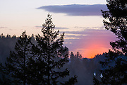 Sunset behind a hillside with trees in the foreground and fog in between. Coeur D Alene, Idaho . PLEASE CONTACT US FOR DIGITAL DOWNLOAD AND PRICING.