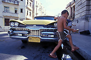 Little kid cleaning a yellow Dodge car, Cuba