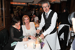 GRIFF RHYS-JONES serving guests EMMA HOCKINGS and CLARE ACE (white top) at One Night Only at The Ivy held at The Ivy, 1-5 West Street, London on 2nd December 2012.