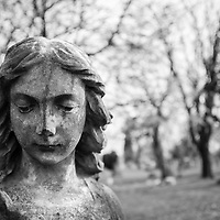 A stone angel at a cemetery, lost deep in thought with blurred trees in the background.