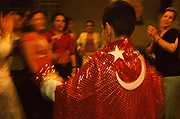 At the henna party of a newly circumcised boy who lives in a suburb of Istanbul, Turkey, the boy dances with a red cloth bearing the emblem of the Turkish flag draped over his shoulders. Female family members and friends clap their hands while he dances.