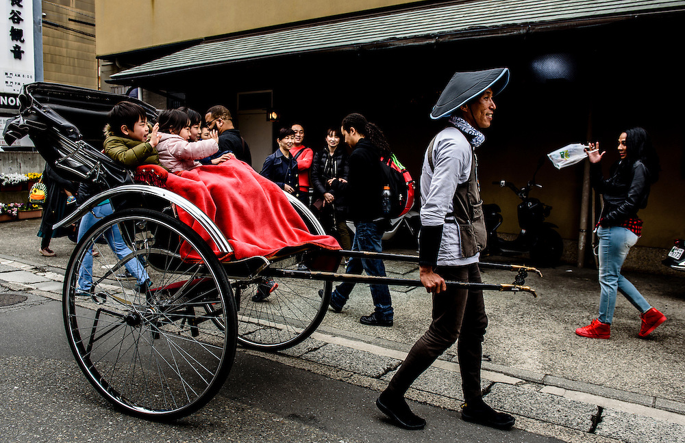 Children ride a rickshaw in Kamakura, Japan.
