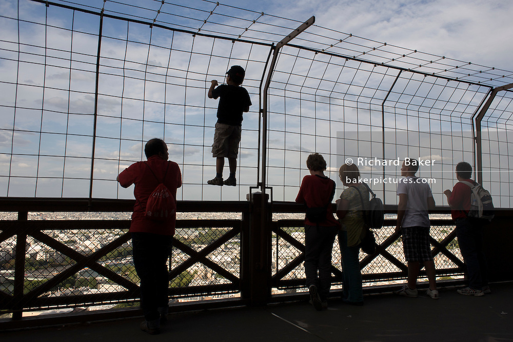 Young tourist climbs up the fence to admire Paris below from the second level of the Eiffel Tower.