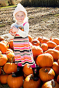 Portrait of a young girl standing on pumpkin