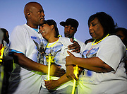 Felton Billoups, from left, comforts his wife Rhonda Billoups over the death of their son Darius Augustus, 17, along with Augustus' uncle Jayson Duncan, back right, and his aunt Pam Duncan, right. Friends and family of the slain teen gathered on the Mississippi River levee where he was killed to honor his memory.