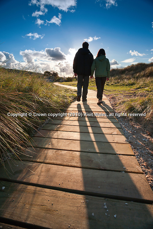Couple walking near Gronant Dunes<br /> Wales Coast Path<br /> Near Prestatyn<br /> Denbighshire<br /> North<br /> Walking<br /> Activities and Sports