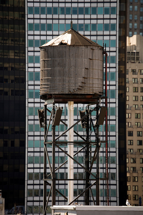 old wooden watertower against the background of a modern high rise in New York city