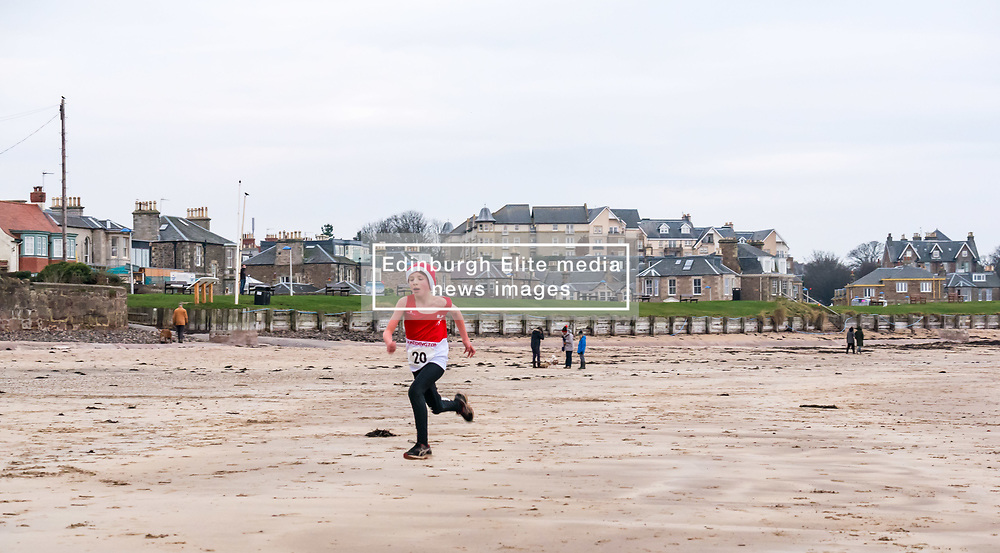 Pictured: Santa Beach Run on the scenic East Lothian coast. This new event is aimed at athletes, casual runners and families. It is hosted by Project Trust with proceeds enabling local school leavers to spend a year volunteering in India/Honduras to teach at a school with few teaching materials. The fastest boy in the children's race. 15 December 2018  <br /> <br /> Sally Anderson | EdinburghElitemedia.co.uk