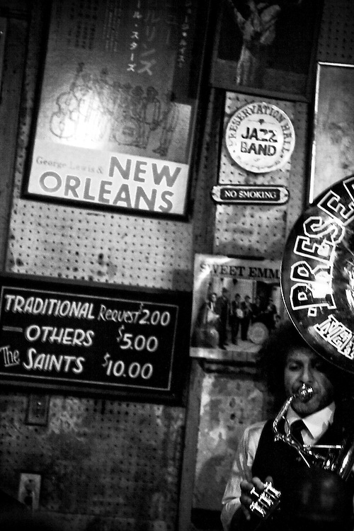Preservation Hall Jazz Band tuba player against wall of history at Preservation Hall in French Quarter of New Orleans, LA.  Copyright 2011 Reid McNally