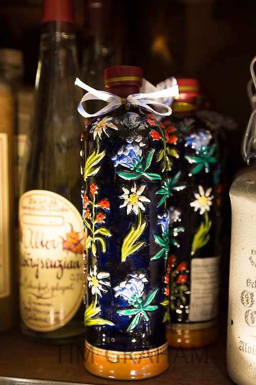 Gentian Brandy, a Bavarian speciality, in floral bottle on display at Dallmayr food store in Munich, Bavaria, Germany