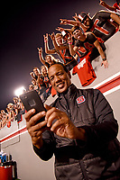 Prior to the start of a football game, men's basketball coach Kevin Keatts takes a selfie with a few of his close friends photo bombing the image.